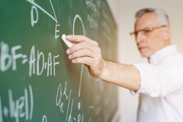 aged-math-teacher-writing-chalkboard_23-2148201011